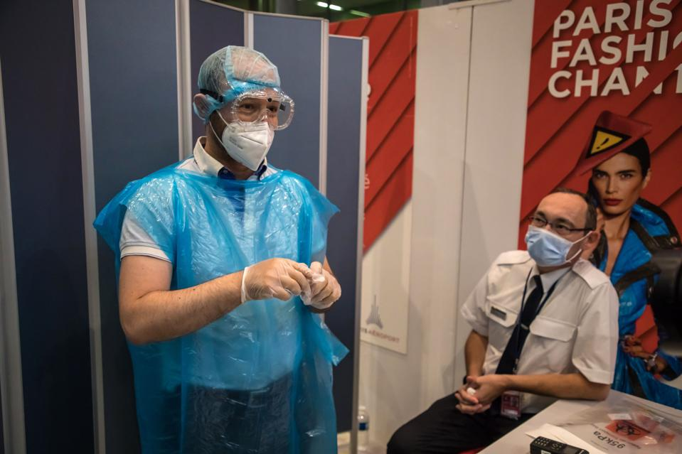 Man in protective gear conducts covid-19 tests at Paris Charles de Gaulle airport France