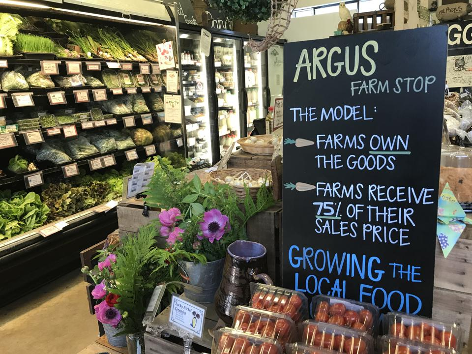 Inside the Argus Farm Stop, with a blackboard sign explaining their model (″Farms own the goods; Farms receive 75% of their sales price. Growing the local food″) next to displays of local fruits, vegetables and flowers.