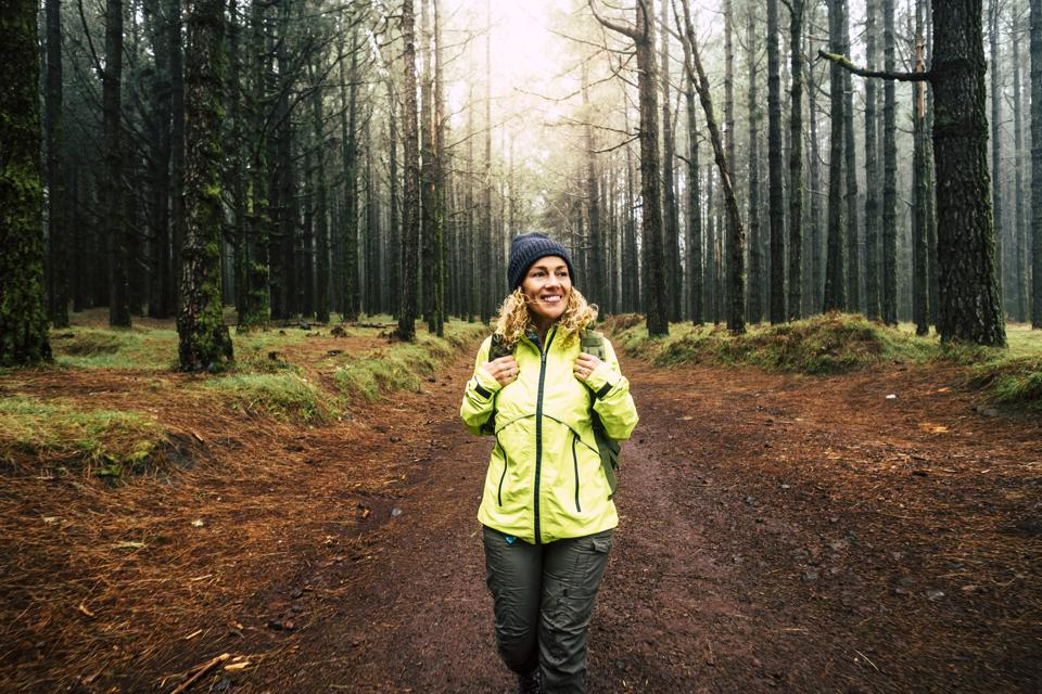 Happy hiker woman smile and enjoy the nature walking in a forest with high trees - alternative outdoor leisure activity and vacation lifestyle - sun in backlight and mist concept
