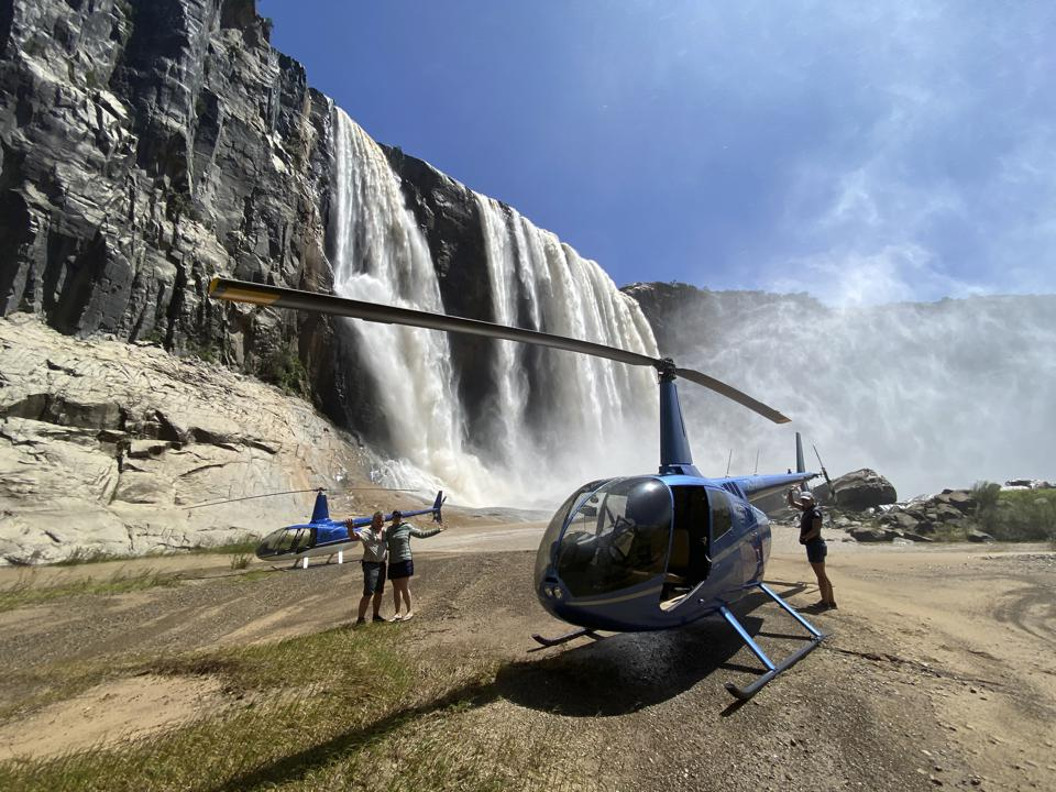 Pilot checks helicopter rotor parked below Howick Falls