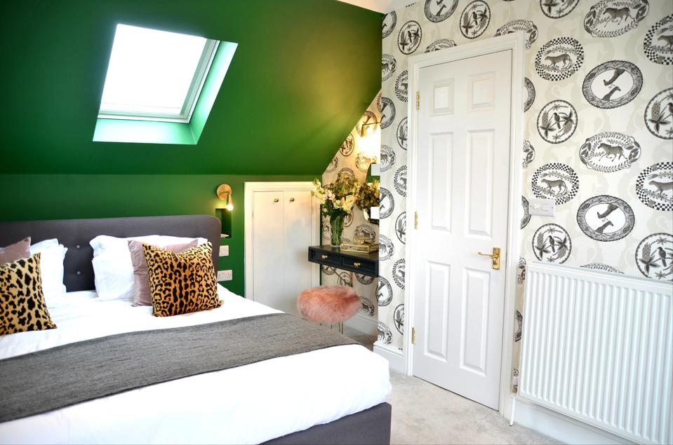 bedroom with green wall and printed wallpaper
