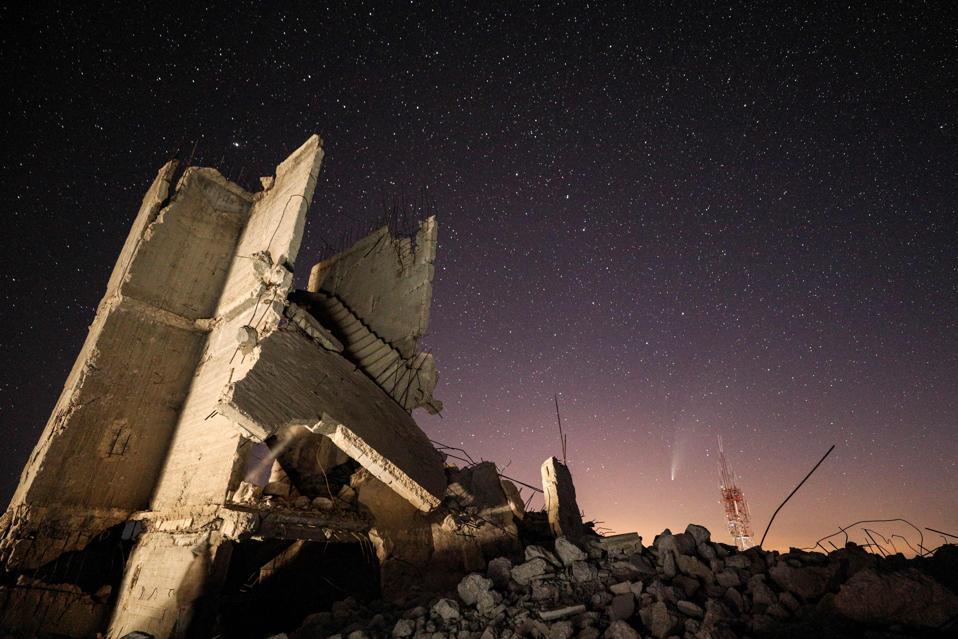 Questa foto a lunga esposizione scattata alla fine del 20 luglio 2020, mostra una vista della cometa NEOWISE (C / 2020 F3) nel cielo sopra edifici distrutti nella città siriana di Ariha nella provincia di Idlib nord-occidentale tenuta dai ribelli.  (Foto di OMAR HAJ KADOUR / AFP via Getty Images)