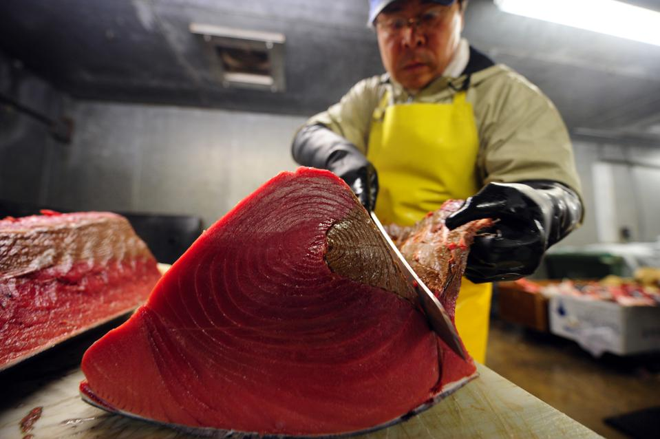 A worker cuts a bluefin tuna into pieces