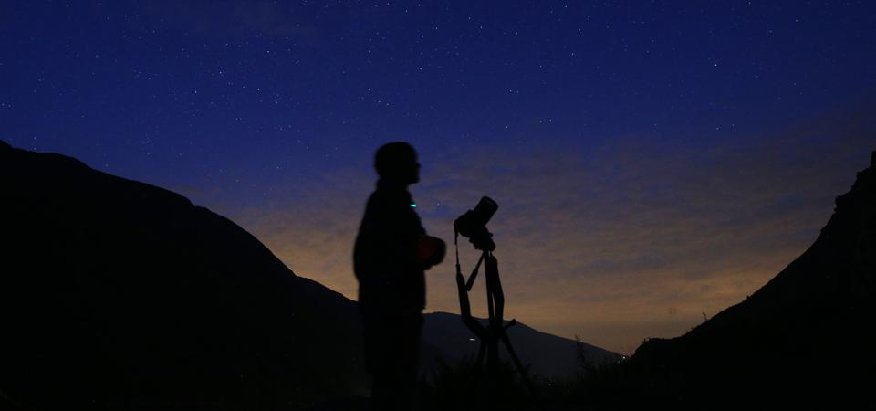 The photographer prepares to take pictures of the annual Perseid meteor shower in northern Italy.  MARCO BERTORELLO / AFP via Getty Images