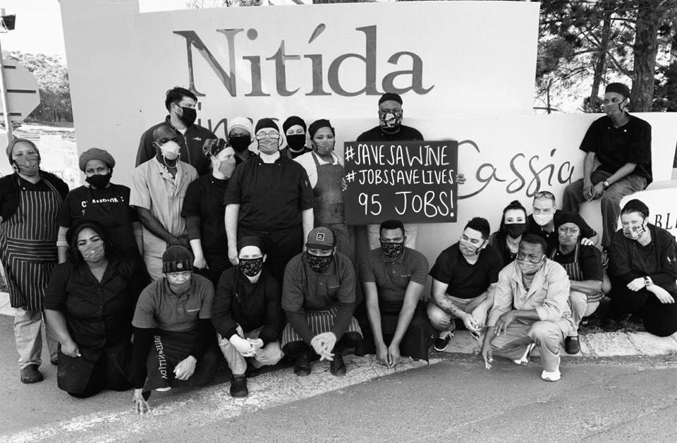 Workers at Nitída Wine Farm in Durbanville hold a placard supporting #SaveSAWine