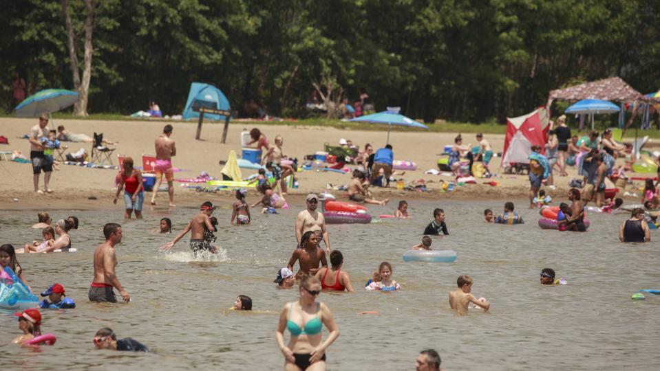 Swimmers fill Lake Monroe at Fairfax Recreation Area beach...