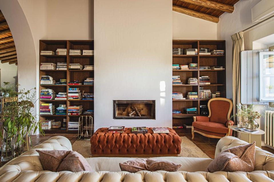 The living room of Malhadinha Nova in Portugal is cozy with tufted couches and bookshelves