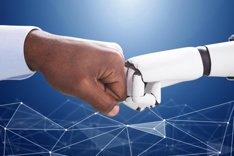 Human hand and a robot hand coming together for a fist bump.