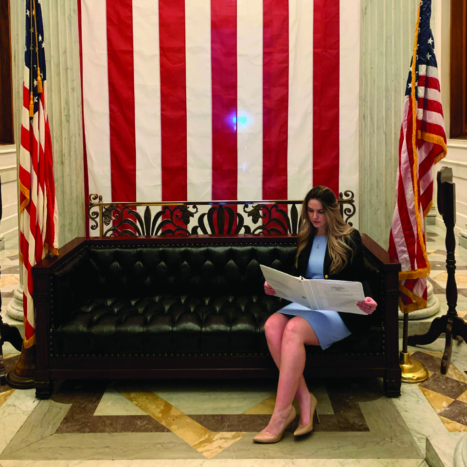 Audrey sitting on soft reading with American Flags surrounding
