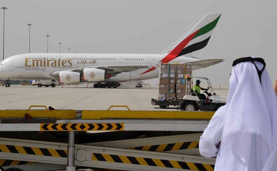 Sheikh watches Emirates airplane at Dubai airport UAE unloading pallets of Covid-19 tests