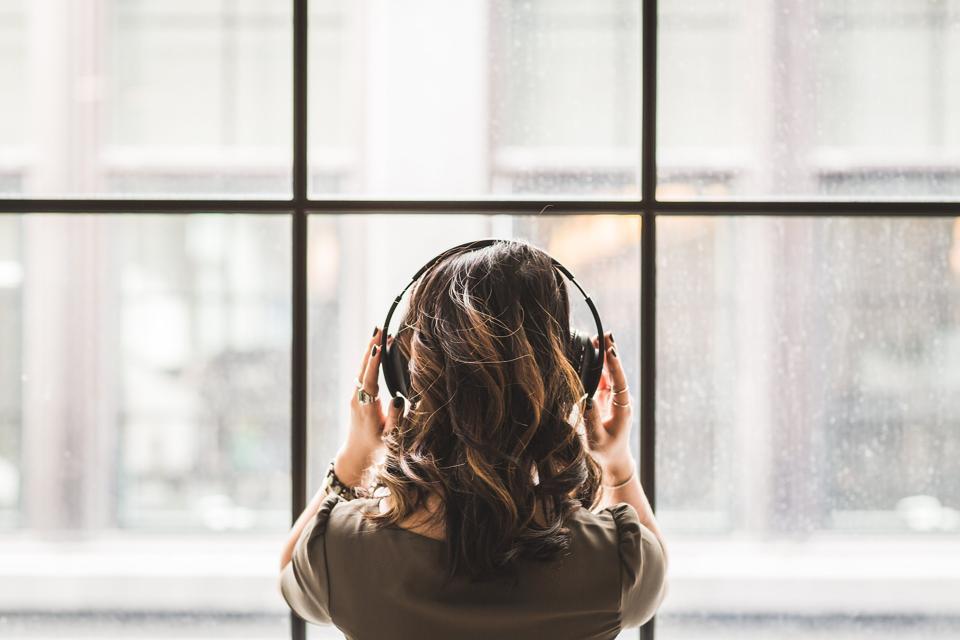Woman listens on headphones
