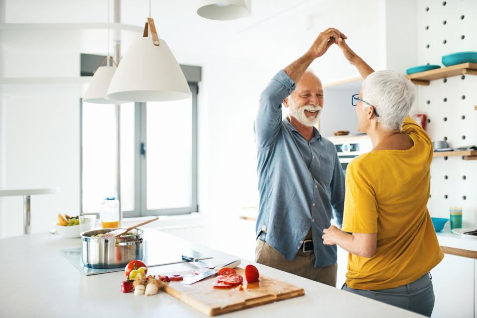 70-something couple having fun while cooking lunch in their Active Adult apartment.