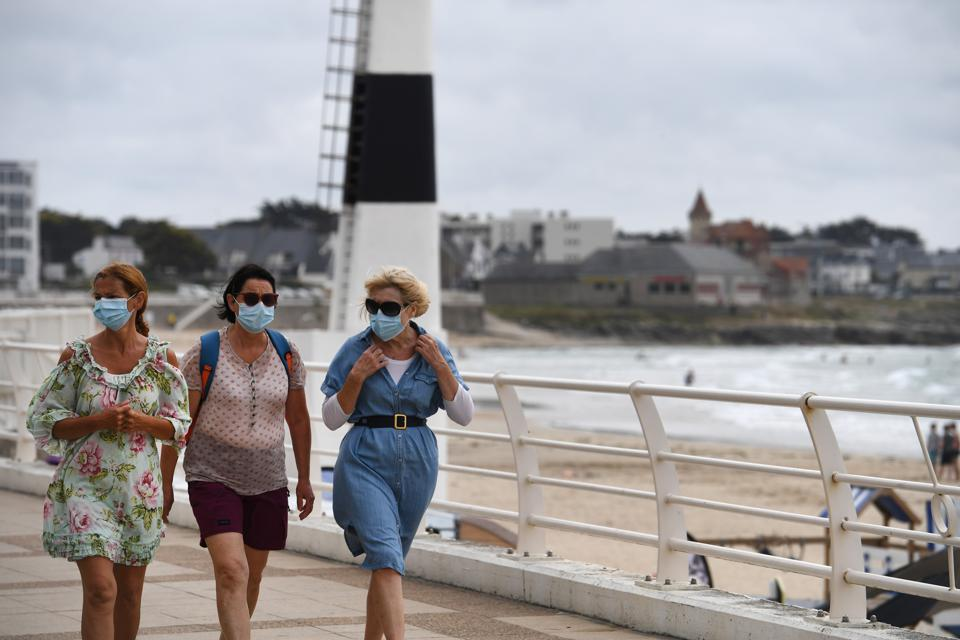 Women wearing mask walk along the seafront on July 27, 2020 in Quiberon, western France.
