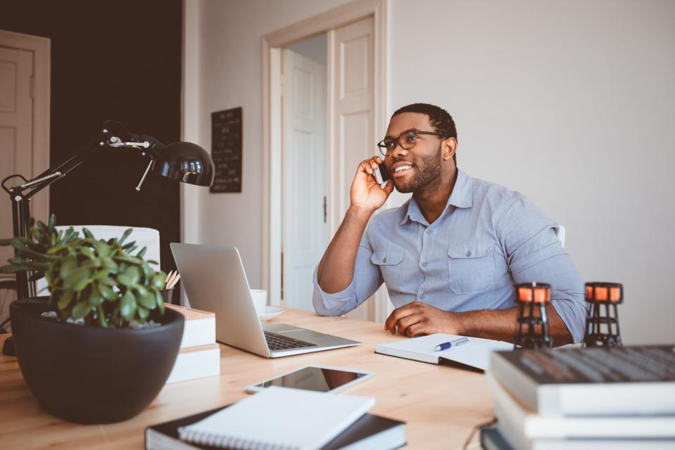 Young businessman at home office talking on phone