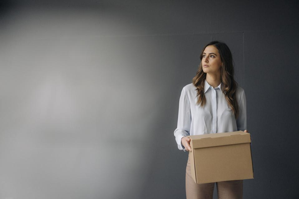 Serious young businesswoman holding cardboard box