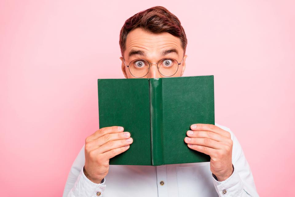 Close up photo portrait of comic cheerful enthusiastic with big staring looking eyes holding paper green book and looking at you isolated pastel background