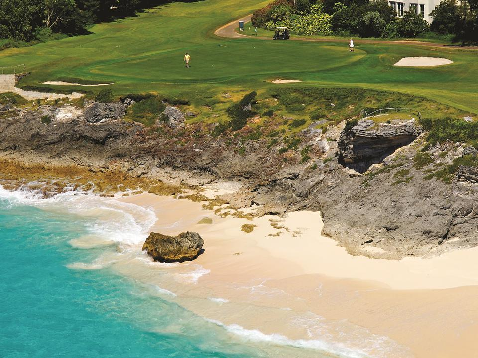 A golf course hole above a pink sand beach