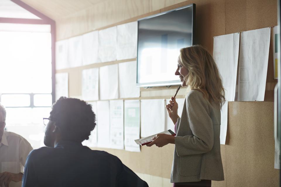 Woman doing presentation, using tablet & screen