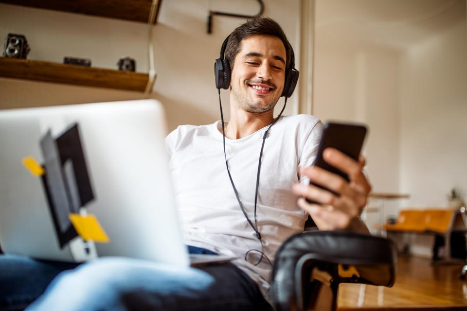 Man relaxing at home with mobile phone and laptop