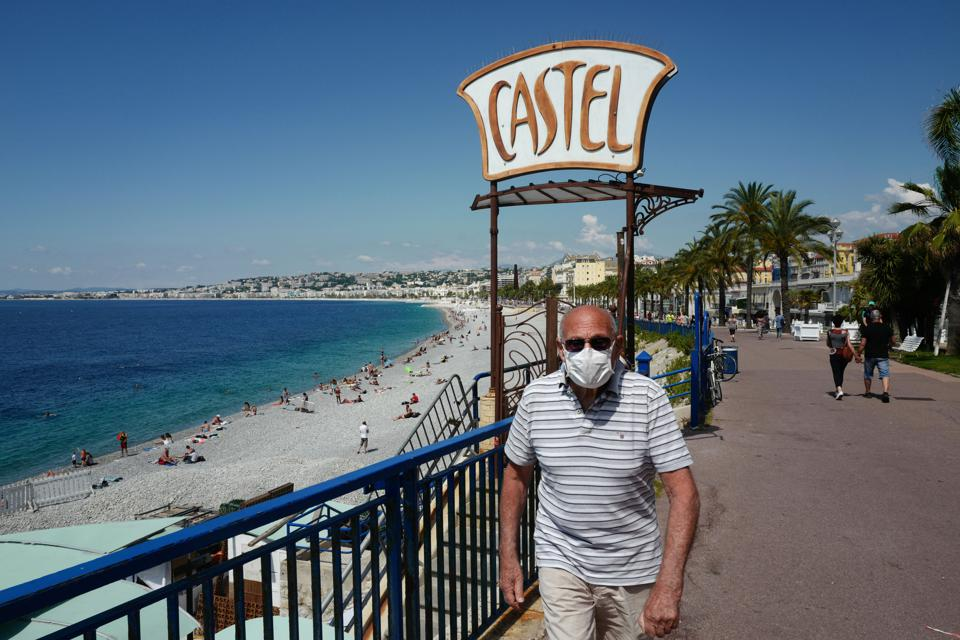 A man wearing a mask walks past Castel beach along the Promenade des Anglais on the French Riviera city of Nice, southern France