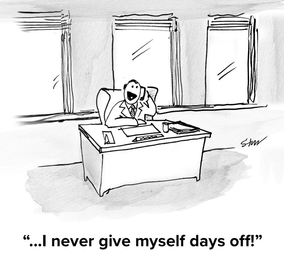 A man sitting by himself at a large office desk on the phone saying ″I never give myself days off!″