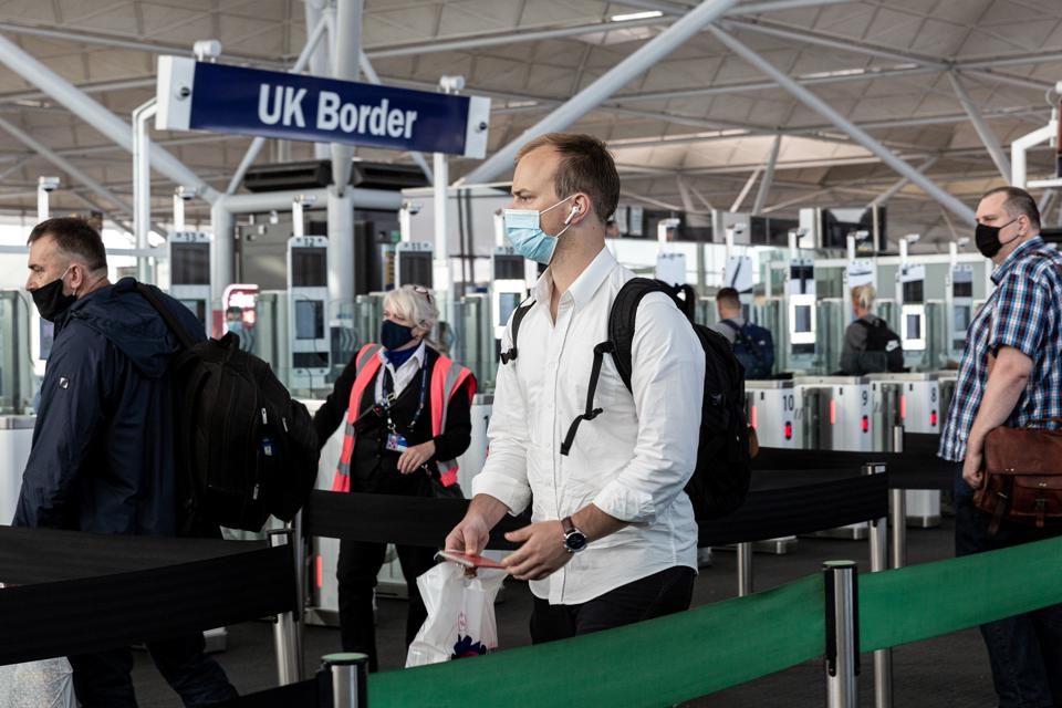 Passengers in protective face masks queue at the passport control after arriving at London Stansted Airport on July 20, 2020.