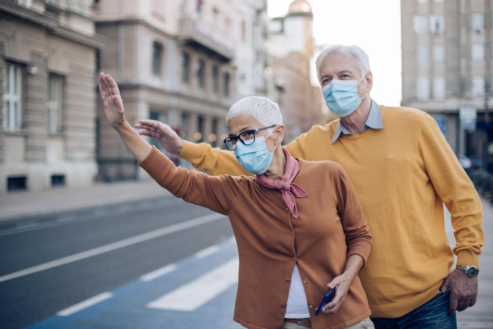 Senior couple wearing protective face mask, waiting for a rides-hare on the street