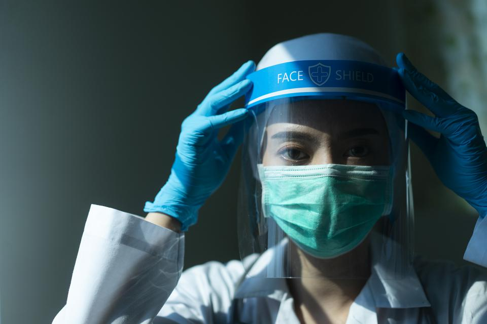Closeup Doctor wearing face shield and PPE suit and praying for stop Coronavirus outbreak or Covid-19, Concept of Covid-19 quarantine