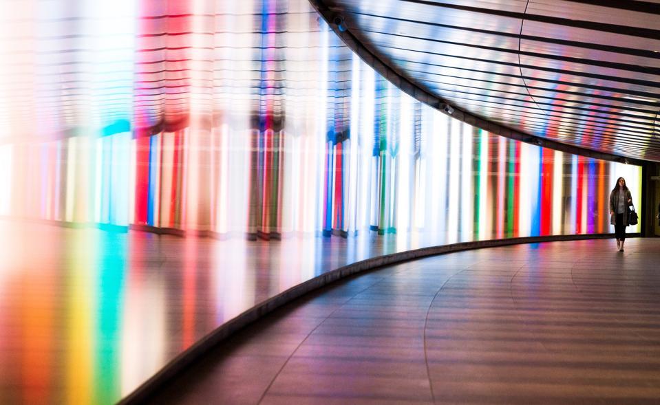 La donna cammina lungo il percorso colorato arcobaleno.  Sarebbe meglio se cantare una melodia.
