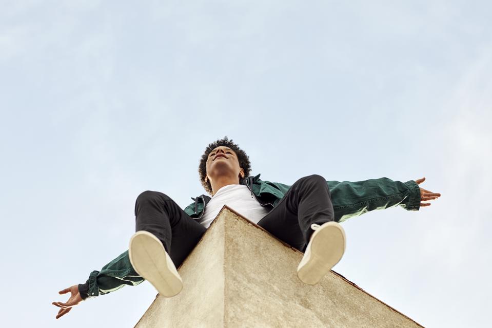 Il giovane uomo di colore si siede sul muro e tiene le braccia al cielo.  Un giorno speriamo che voli.