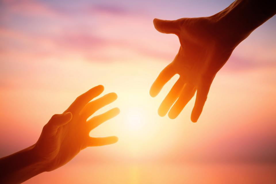 Giving a helping hand on the background of the dawn