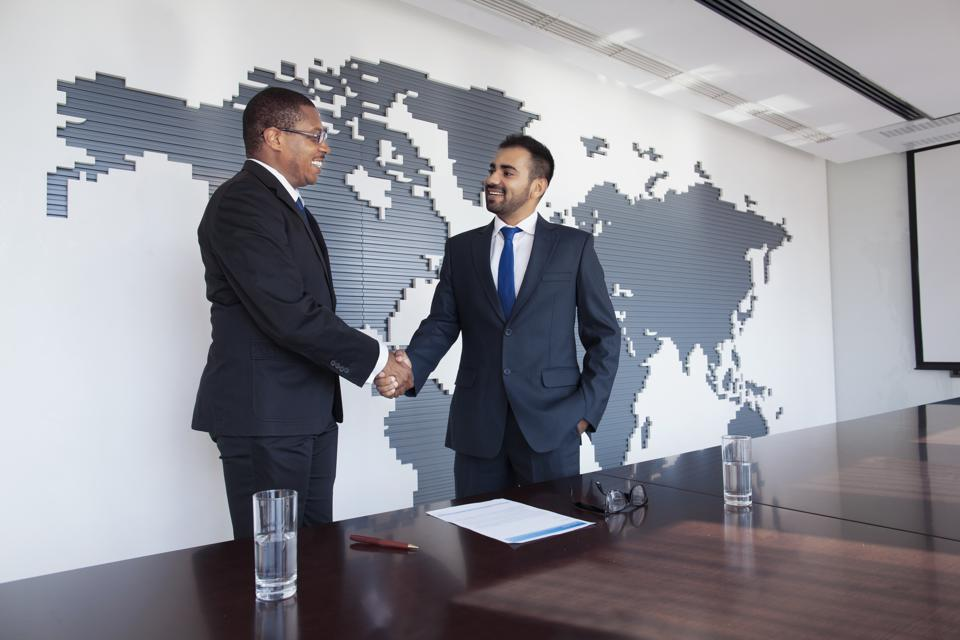 Businessmen shaking hands at conference table