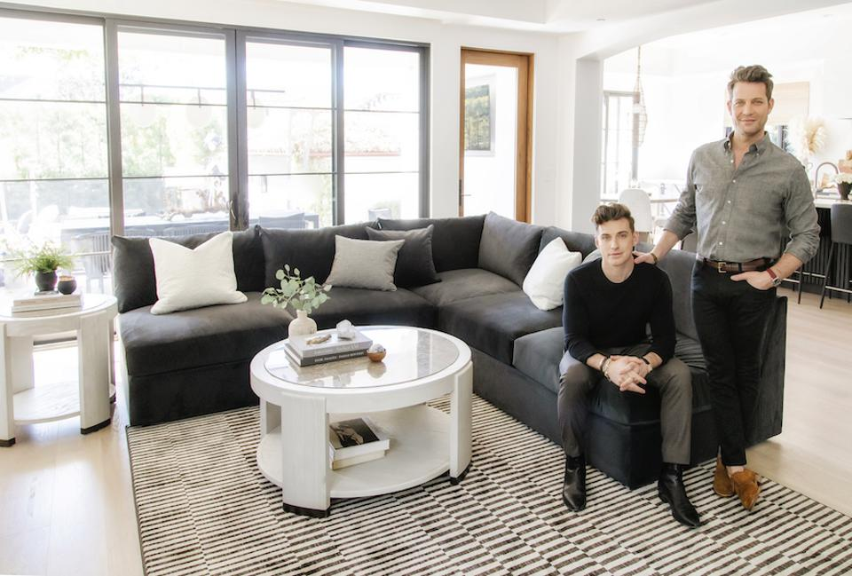 Nate Berkus and Jeremiah Brent sit on a sofa in a living room.