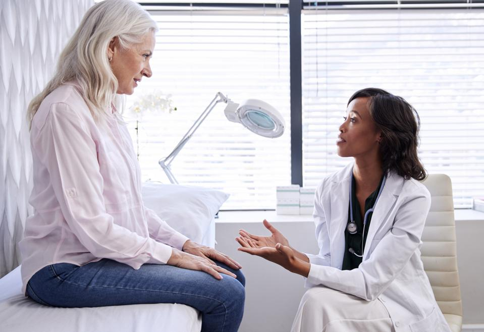 Woman sitting on examination bed in doctor's office, speaking to her doctor.