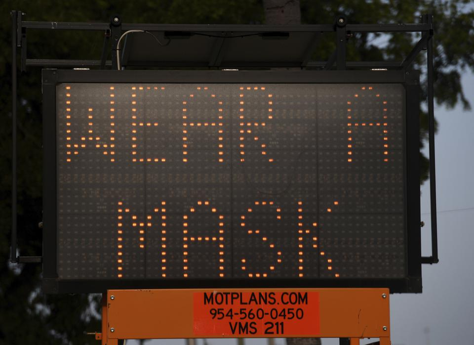 A sign in Florida advises residents to ″wear a mask″ to slow the spread of coronavirus.