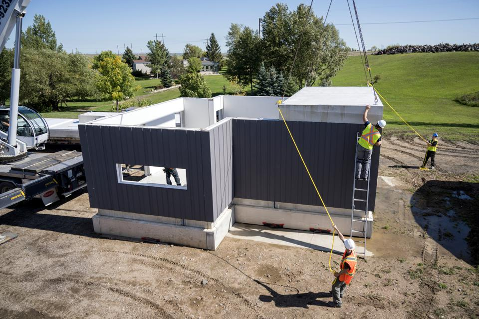 Construction workers assembling a building made with Nexii's Nexiite concrete alternative