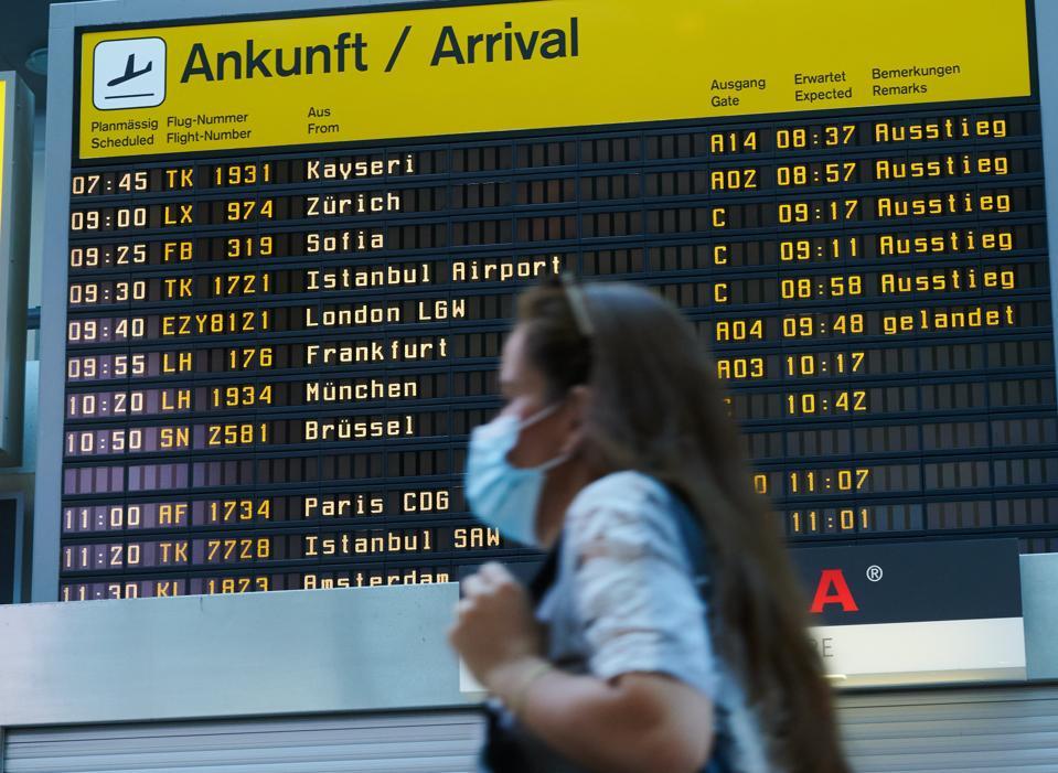 Traveler in mask walks past arrival board at Berlin Tegel Airport Europe