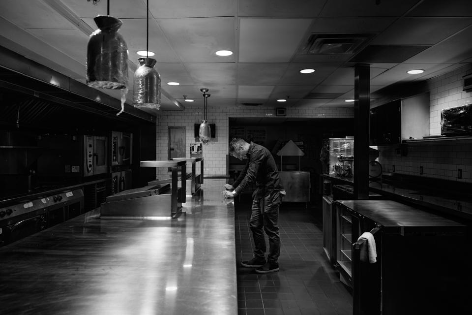 Bobby Stuckey stands in an empty restaurant kitchen
