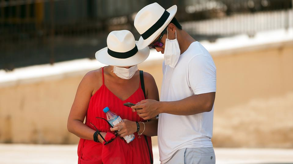 A couple of tourists wearing face masks as a precaution,...
