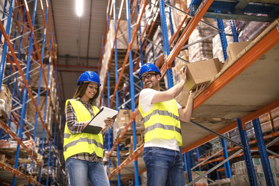 Two smiling people working together in warehouse storage facility. Checking goods at distribution warehouse.
