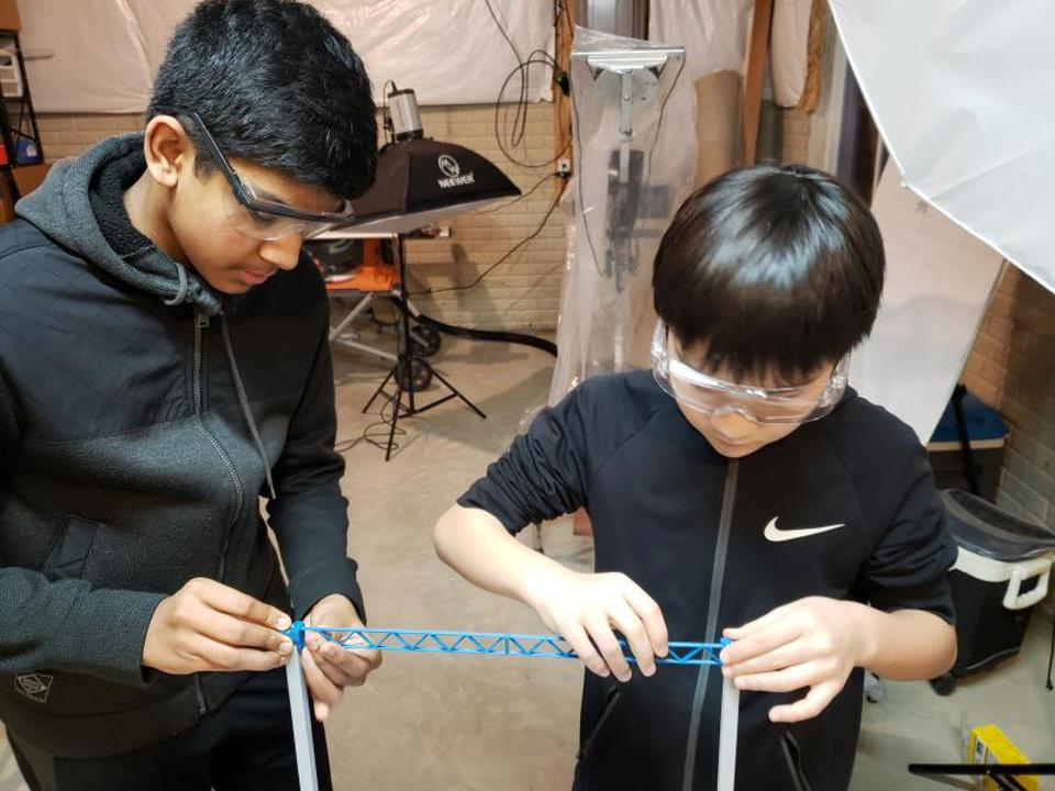 Two kids work on a prototype.