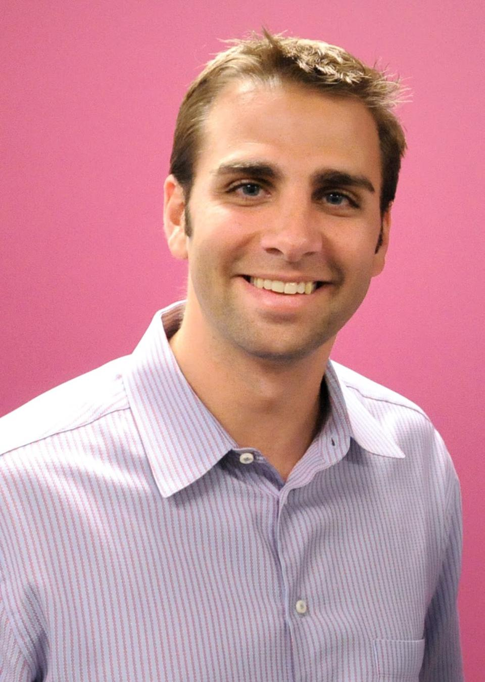 Genomatica co-founder and CEO Christophe Schilling in a collared shirt, smiling.