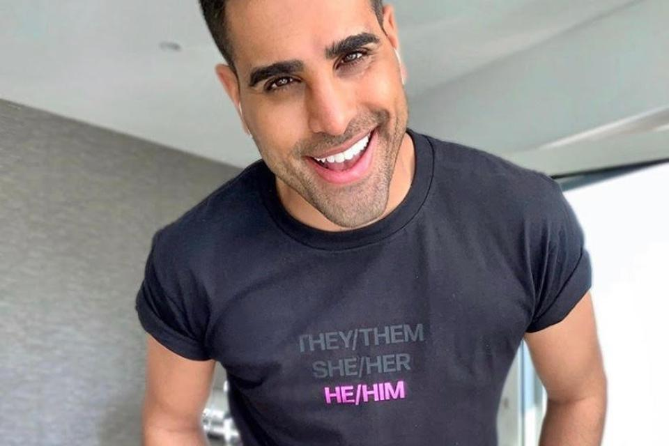 TV personality Dr Ranj wearing a pronouns t-shirt, showing solidarity with the trans community