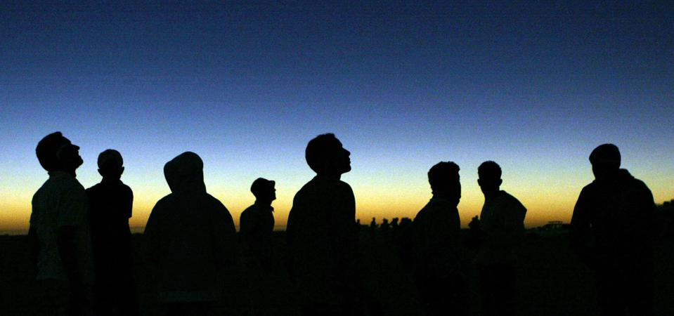 Libyan youths watch the solar eclipse in the desert tourist camp in Galo, 1300 km south of the Libyan capital of Tripoli, 29 March 2006. KHALED DESOUKI/AFP via Getty Images