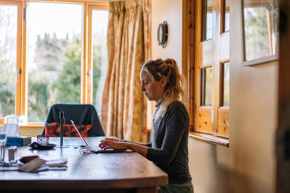Young woman uses laptop computer on kitchen table