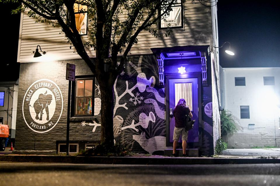A purple light hangs over a dimly lit doorway beside a painted sign reading ″Black Elephant Hostel.″