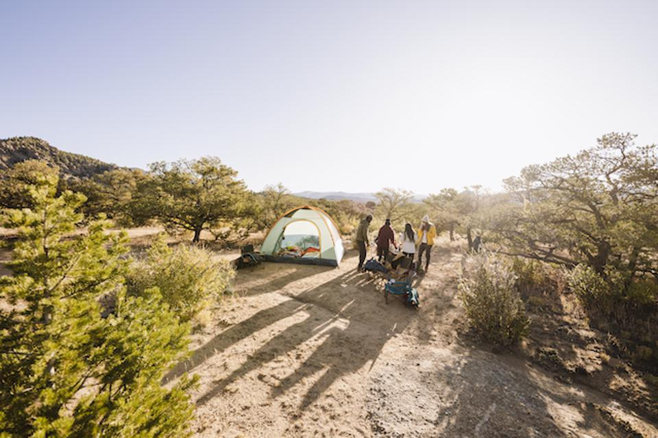 A tent in a desert landscape with people outside