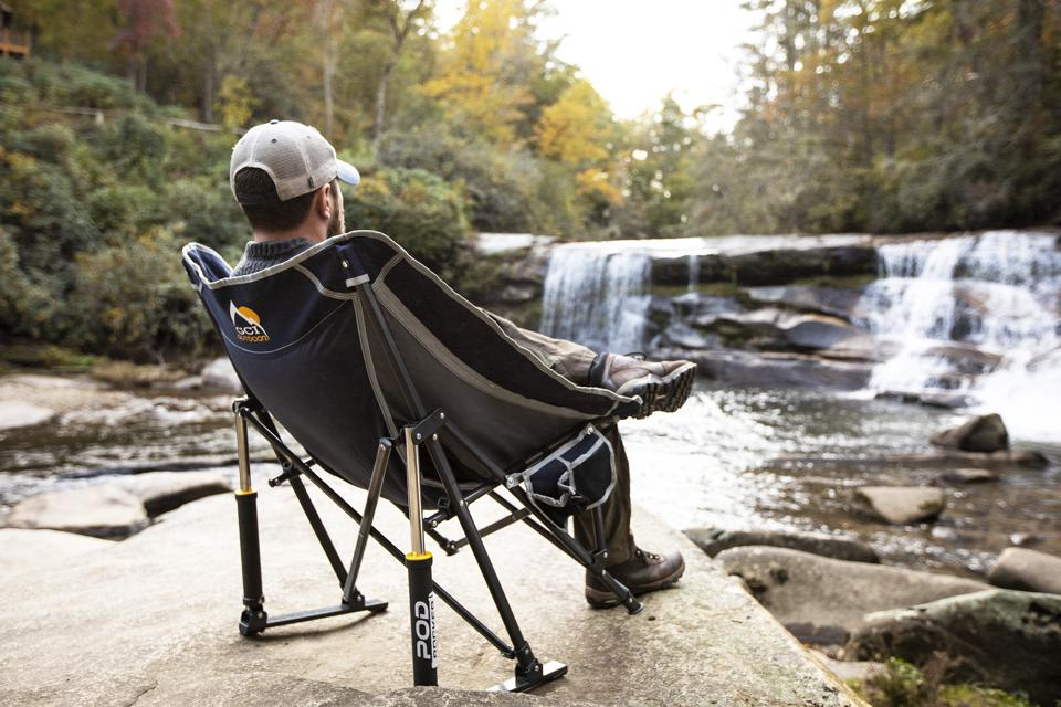 Man sitting in a folding chair looking at a waterfall