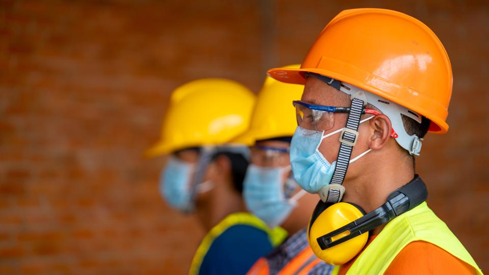 construction workers standing in a line with face masks on