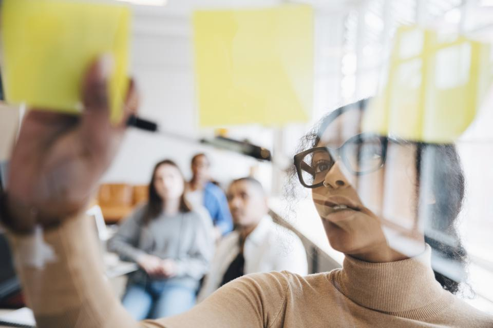 Female computer hacker sticking adhesive notes on glass with colleagues sitting in background